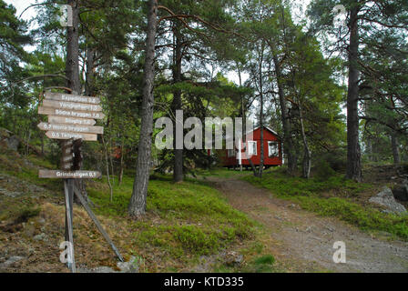 Signposts in front of red house on Grinda island near Stockholm - Stock Photo