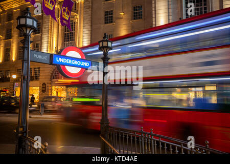Double Decker bus moves along the Regent Street at night near the Piccadilly Circus underground station entrance - Stock Photo
