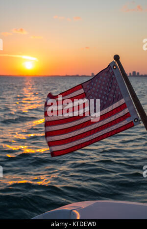 American flag behind boat, sunset and city in background - Stock Photo