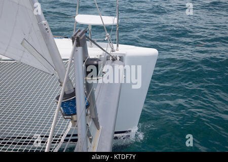 Charter catamaran sailboat bow moves through blue water - Stock Photo