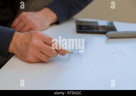 Architect draws a plan projection initial preparatory stage in construction new building - Stock Photo