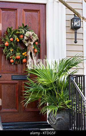 A traditional low country Christmas wreath decorated with fruit hangs from a wooden door on a historic home along - Stock Photo