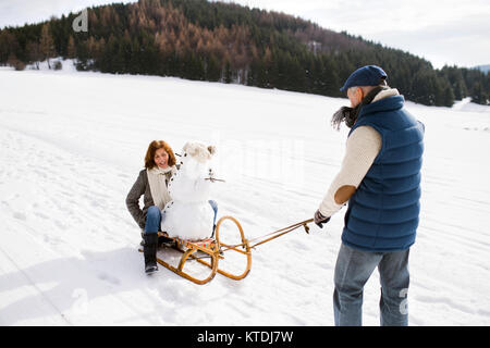 Senior couple with snowman on sledge in winter landscape - Stock Photo