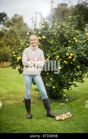 Portrait of smiling young woman at quince tree in garden - Stock Photo