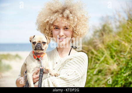Portrait of smiling young woman holding dog on her arms - Stock Photo