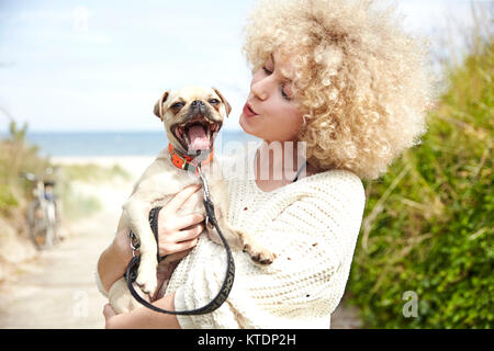 Portrait of young woman holding dog on her arms - Stock Photo