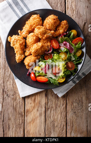 deep-fried chicken wings in breadcrumbs and fresh vegetable close-up on a plate. Vertical top view from above - Stock Photo