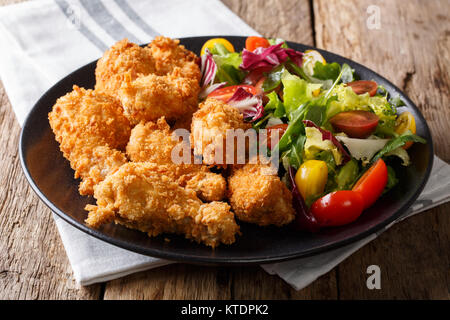 Fried chicken wings in breadcrumbs and fresh vegetable salad close-up on a plate. horizontal - Stock Photo