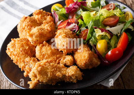 Spicy deep-fried chicken wings in breadcrumbs and fresh vegetable salad close-up on a plate. horizontal - Stock Photo