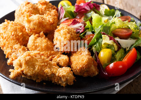 deep-fried chicken wings in breadcrumbs and fresh vegetable close-up on a plate. horizontal - Stock Photo