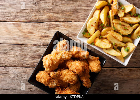 Fried chicken wings in bread crumbs and potato wedges close up on the table. horizontal top view from above - Stock Photo