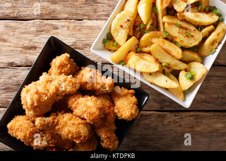 Delicious food: deep-fried chicken wings in breadcrumbs and potato close-up on the table. Horizontal top view from - Stock Photo