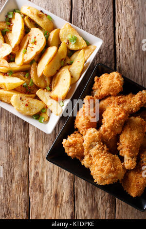 Delicious food: deep-fried chicken wings in breadcrumbs and potato close-up on the table. Vertical top view from - Stock Photo