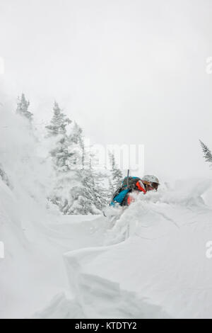 Skier freerider jumping from a snow ramp in the sun on a background of forest and mountains. - Stock Photo