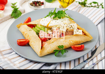 French cuisine. Breakfast, lunch, snacks. Pancakes with egg poached, feta cheese, fried ham, avocado and tomatoes - Stock Photo