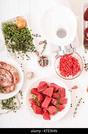 Chopped raw meat. The process of preparing forcemeat by means of a meat grinder. Homemade sausage. Ground beef. - Stock Photo