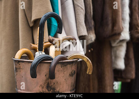 Coats hanging on an iron frame with wooden canes. These are vintage clothes but are back in fashion. - Stock Photo