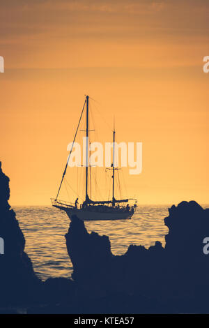 Silhouette of a sailboat at sunset sailing from Newport Beach, California with Santa Catalina Island in the background - Stock Photo