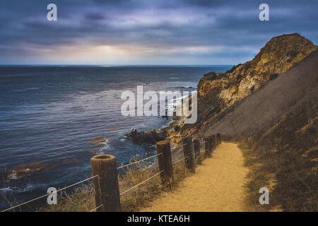 Coastal hiking trail cascading down the steep cliffs of Pelican Cove Park on a cloudy day with beams of sunlight - Stock Photo