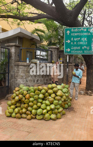 A street vendor standing near heap of coconuts while selling to customer on the street, information sign in background - Stock Photo