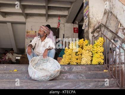 Market porter sitting with basket on steps of city market beside heap of bananas in Bangalore, Bengaluru, Karnataka, - Stock Photo