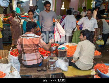 Market vendor weighing flowers while selling to customer at Sri Krishna Rajendra Market in Bangalore, Bengaluru, - Stock Photo