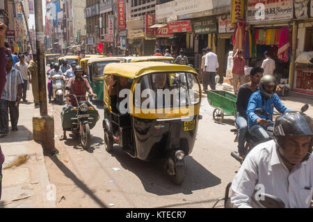 Auto rickshaw and vehicles moving on busy street, people walking on pavement in Bangalore, Bengaluru, Karnataka, - Stock Photo