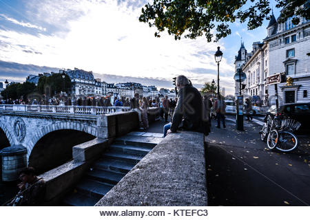 Tourists and locals gather at dusk at the Pont Saint-Michel along the banks of the Seine River on the Ile de la - Stock Photo