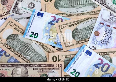 various currencies on the table, banknotes from different countries overlapping each other - Stock Photo