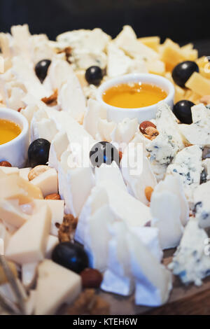 Cheese plate. Assortment of cheese with walnuts and honey from honey dipper on white wood serving board over white - Stock Photo