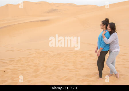 Two girls of different ethnicity having fun in the desert on Dune 7, Walvis Bay, Namibia - Stock Photo