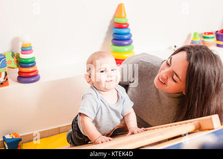 Young mother supports the baby, helping him climb the ladder in kindergarten - Stock Photo