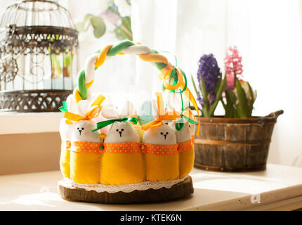 Easter decorations - textile basket with rabbits and eggs, morning light from window - Stock Photo