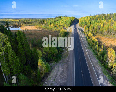 Small lake between swamps and asphalt road passing near in autumn forests of Karelia, Russia - Stock Photo