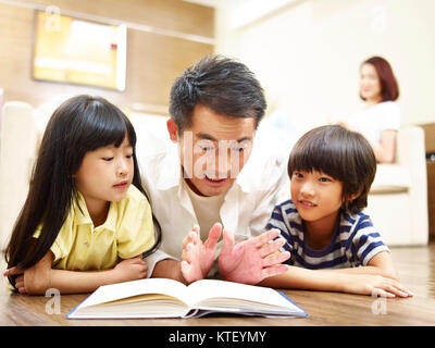 asian father and two children lying on front on floor reading book while mother watching in the background. - Stock Photo