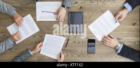 Business people discuss contract sitting around office table, top view - Stock Photo