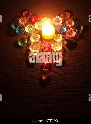 Burning candle. Candles laid out around the colored transparent stones in the form of heart. Still life. - Stock Photo