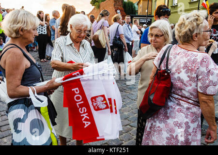 Old women selling Polish flags on Warsaw uprising Remembrance Day. Warsaw, Poland. On August 1st, 1944 Warsaw attempted - Stock Photo