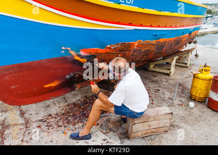 Man repairing a traditional luzzu boat at Marsaxlokk harbour, Malta - Stock Photo