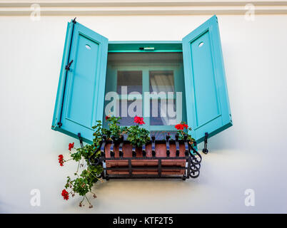 Geranium red flowers on the window with blue color shutters on vintage  house, Alacati, Turkey - Stock Photo
