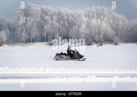 snowmobile on the snow. driver of a snowmobile heading South on the frozen lake on the background of the winter - Stock Photo