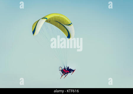 yellow paraglide flying over clear blue winter sky. paraglider with a passenger. Adventure man active extreme sports - Stock Photo