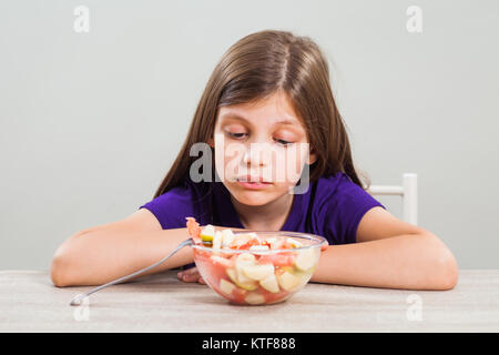 Little girl does not like to eat fruit salad. - Stock Photo