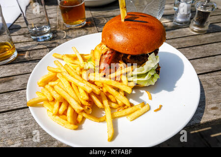 Obesity: Typical British pub food: a beefburger in a bun with cheese and bacon and a pile of golden French fries, - Stock Photo