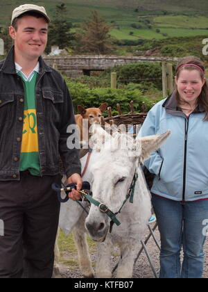 Local Irish folks and small donkey along the side of the road. - Stock Photo