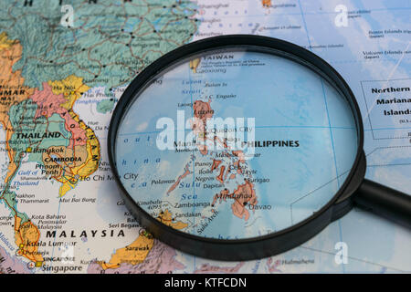 the Philippines map through magnifying glass on a world map - Stock Photo