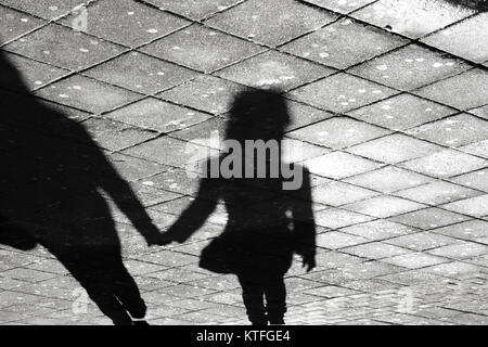 Mother and daughter holding hands  shadow , on city street sidewalk in black and white - Stock Photo
