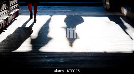 Teenage girl in red tights approaching with a shadow in the subway passage , and other people shadows going down - Stock Photo
