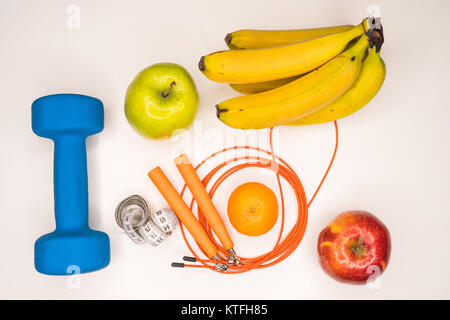 healthy eating concept. Dumbbell, rope, bananas, orange, measuring tape waist, oranges, red apple, green apple, - Stock Photo