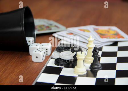 mix of goblet table games dice spanish poker cards chess and checkers - Stock Photo